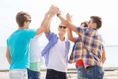 Groupe d'amis de sourire faisant la haute cinq dehors Photo stock