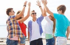 Groupe d'amis de sourire faisant la haute cinq dehors Image libre de droits