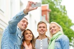 Groupe d'amis de sourire faisant le selfie dehors Photographie stock
