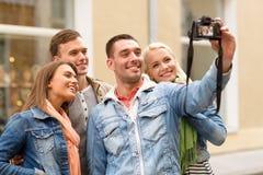 Groupe d'amis de sourire faisant le selfie dehors Photographie stock libre de droits