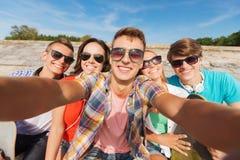 Groupe d'amis de sourire faisant le selfie dehors Photos stock