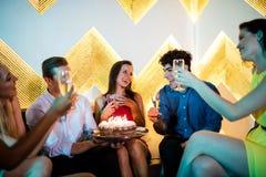 Groupe d'amis de sourire grillant un verre de champagne tout en célébrant l'anniversaire Images stock