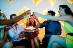 Groupe d'amis de sourire grillant un verre de champagne tout en célébrant l'anniversaire Photo stock
