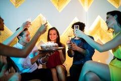 Groupe d'amis de sourire grillant un verre de champagne tout en célébrant l'anniversaire Photos libres de droits