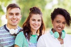 Groupe d'amis de sourire heureux avec des écouteurs Photo stock