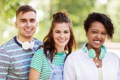 Groupe d'amis de sourire heureux avec des écouteurs Photos stock