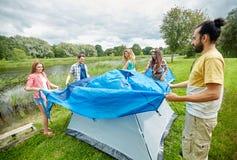 Groupe d'amis de sourire installant la tente dehors Photographie stock