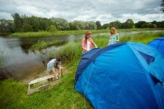 Groupe d'amis de sourire installant la tente dehors Photographie stock libre de droits