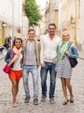 Groupe d'amis de sourire marchant dans la ville Images libres de droits