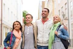 Groupe d'amis de sourire marchant dans la ville Photographie stock libre de droits