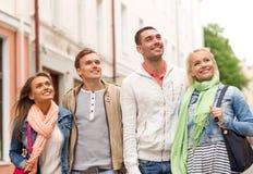 Groupe d'amis de sourire marchant dans la ville Photographie stock