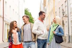 Groupe d'amis de sourire marchant dans la ville Image stock