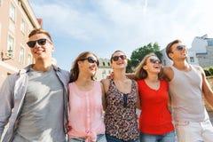Groupe d'amis de sourire marchant dans la ville Photo stock
