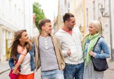 Groupe d'amis de sourire marchant dans la ville Image libre de droits