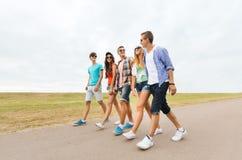 Groupe d'amis de sourire marchant sur la route Images stock