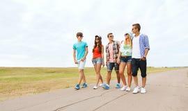 Groupe d'amis de sourire marchant sur la route Photographie stock libre de droits
