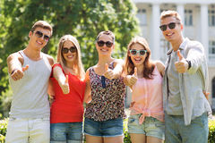 Groupe d'amis de sourire montrant des pouces  Image stock