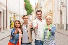 Groupe d'amis de sourire montrant des pouces  Photos libres de droits