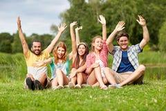 Groupe d'amis de sourire ondulant des mains dehors Photographie stock