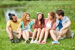 Groupe d'amis de sourire parlant dehors Photos stock
