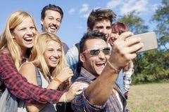 Groupe d'amis de sourire prenant le selfie Photos stock