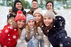 Groupe d'amis de sourire prenant le selfie dehors Image stock