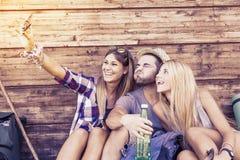 Groupe d'amis de sourire prenant le selfie drôle Image libre de droits