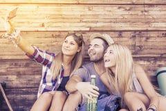 Groupe d'amis de sourire prenant le selfie drôle Photos stock