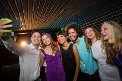 Groupe d'amis de sourire prenant un selfie de téléphone portable Photos stock