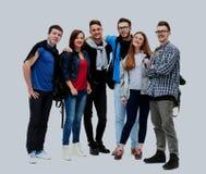 Groupe d'amis de sourire restant ensemble et regardant l'appareil-photo d'isolement sur le fond blanc Photographie stock