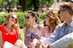 Groupe d'amis de sourire s'asseyant dehors en parc Images stock