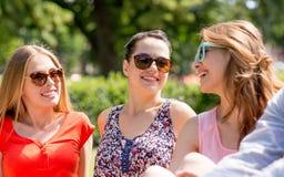 Groupe d'amis de sourire s'asseyant dehors en parc Images libres de droits