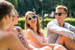 Groupe d'amis de sourire s'asseyant dehors en parc Photographie stock libre de droits