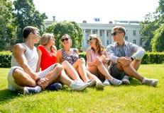 Groupe d'amis de sourire s'asseyant dehors en parc Photo stock