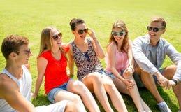 Groupe d'amis de sourire s'asseyant dehors en parc Image stock