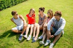 Groupe d'amis de sourire s'asseyant dehors en parc Photographie stock