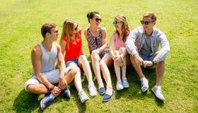Groupe d'amis de sourire s'asseyant dehors en parc Photos stock