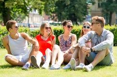 Groupe d'amis de sourire s'asseyant dehors sur l'herbe Photos libres de droits