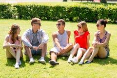 Groupe d'amis de sourire s'asseyant dehors sur l'herbe Photographie stock libre de droits
