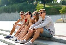 Groupe d'amis de sourire s'asseyant sur la place de ville Photos stock
