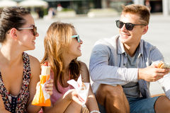 Groupe d'amis de sourire s'asseyant sur la place de ville Photos libres de droits