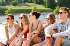 Groupe d'amis de sourire s'asseyant sur la place de ville Photo libre de droits