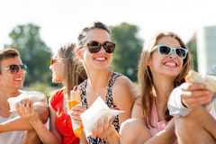 Groupe d'amis de sourire s'asseyant sur la place de ville Images stock