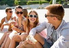 Groupe d'amis de sourire s'asseyant sur la place de ville Photographie stock libre de droits