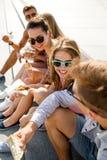 Groupe d'amis de sourire s'asseyant sur la place de ville Photo stock