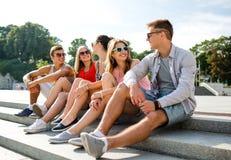 Groupe d'amis de sourire s'asseyant sur la rue de ville Photos stock