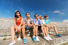 Groupe d'amis de sourire s'asseyant sur la rue de ville Image stock