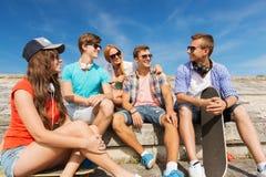 Groupe d'amis de sourire s'asseyant sur la rue de ville Photographie stock libre de droits