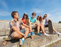 Groupe d'amis de sourire s'asseyant sur la rue de ville Photos libres de droits