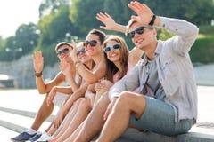 Groupe d'amis de sourire s'asseyant sur la rue de ville Photo libre de droits